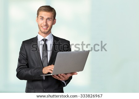 Young handsome businessman holding laptop - stock photo
