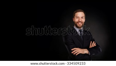 Young handsome businessman in a suit with great smile against black background with lots of copy space - stock photo