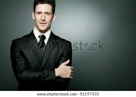 Young handsome businessman in black suit. - stock photo