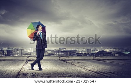 Young handsome businessman in suit with colorful umbrella - stock photo