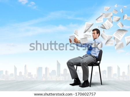 Young handsome businessman looking with astonishment in tablet pc - stock photo