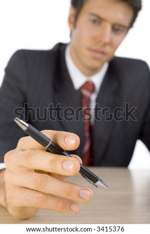 Young, handsome businessman. Seating behind desk and holding a pen. Looking at pen. White background, front - stock photo