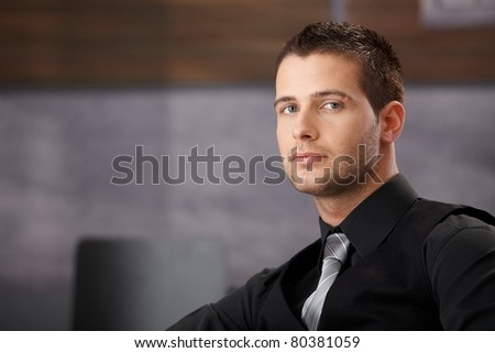 Young handsome businessman sitting in modern office.? - stock photo