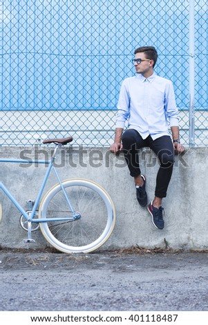 Young handsome businessman sitting on low wall - stock photo