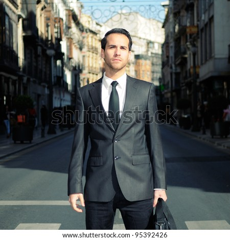 Young handsome businessman standing in a crosswalk - stock photo