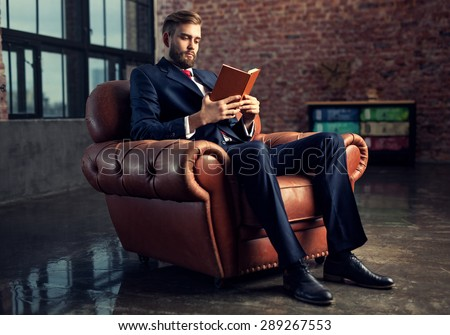 Young handsome businessman with beard in black suit sitting on chair reading book. Focus on face. - stock photo