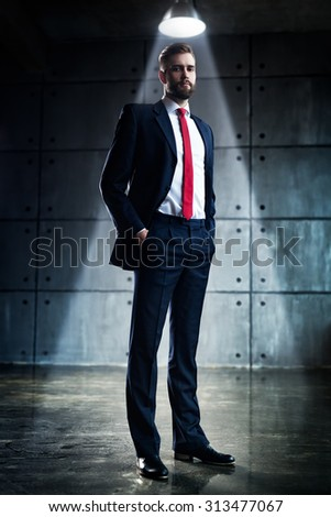 Young handsome businessman with beard in black suit standing under bright light in urban interior. - stock photo