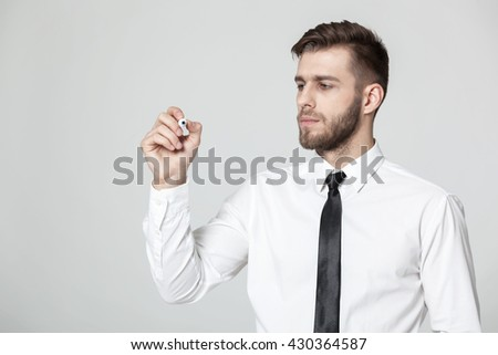 Young handsome businessman writing  on a transparent pane - copyspace. - stock photo