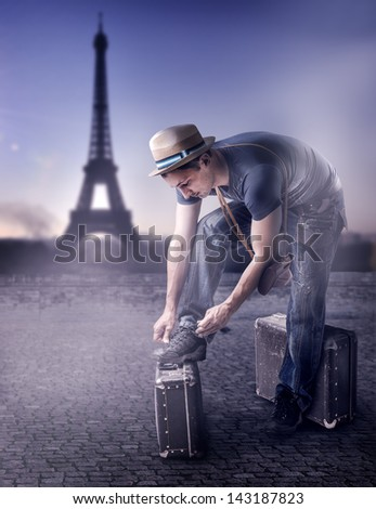 Young handsome casual man Traveler in a straw hat with old brown suitcase wearing dress read guide to Paris, France - stock photo