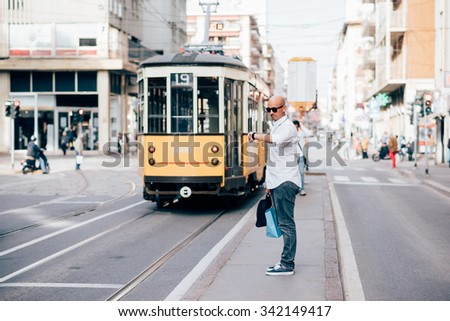 Young handsome caucasian bald business man standing on a bus stop, looking down his wrist watch - delay, work, waiting concept - stock photo