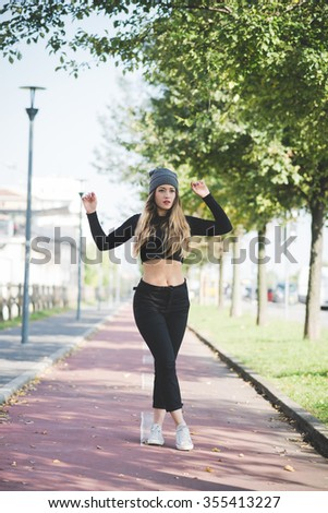 young handsome caucasian blonde straight hair woman model posing outdoor in the city, overlooking left, legs crisscrossed, arms up, serious - pensive, thinking future concept - stock photo