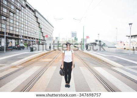 young handsome caucasian brown straight hair woman posing in the street of the city, looking in camera, serious - pensive, thoughtful concept - stock photo