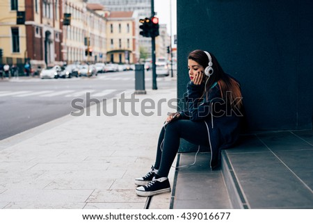 young handsome caucasian reddish straight hair woman sitting on a step, listening music with headphones, looking downward, pensive - serious, thoughtful concept - stock photo