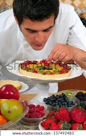 Young handsome chef making fruit tarts - stock photo
