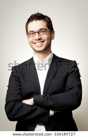 Young handsome confident man in black suit and glasses smiling - stock photo