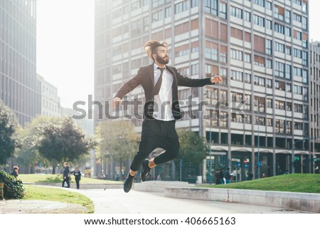 Young handsome contemporary business man jumping outdoor in city back light - success, positive, winner concept - stock photo