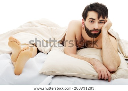 Young handsome depressed man in bed. - stock photo