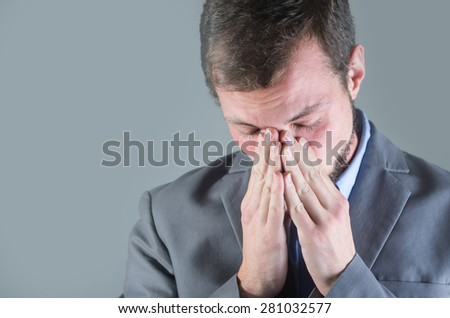 Young handsome desperate man, covering his face with his hands, looking down - stock photo