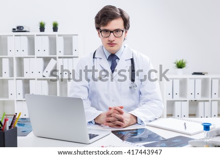 Young handsome doctor sitting at desk with laptop and x-rays in his office with plants on shelves in the background - stock photo