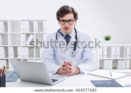 Young handsome doctor sitting at desk with laptop and x-rays in his office with shelves in the background - stock photo