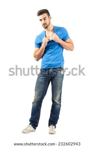 Young handsome fashion model holding t-shirt collar. Full body length isolated over white background. - stock photo