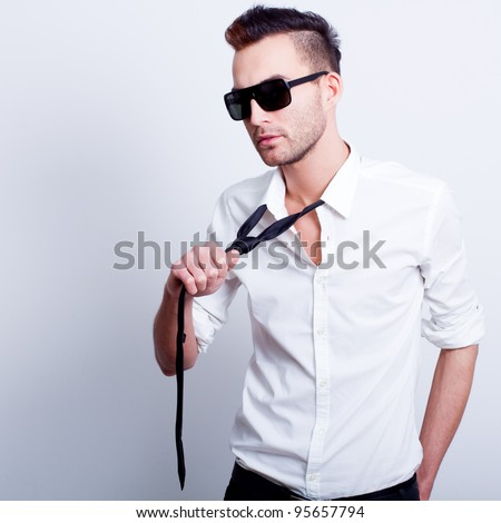 young handsome fashion model man posing in white shirt with black pulled tie - stock photo