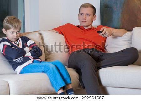 Young handsome father watching television and his angry son - stock photo
