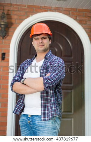 Young handsome foreman in hardhat posing against new built house - stock photo