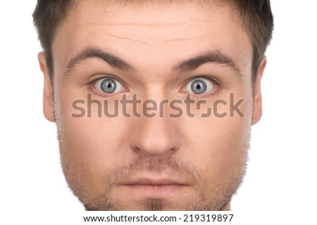 Young handsome funny man on white background. cool guy looking into camera with eyes wide open - stock photo