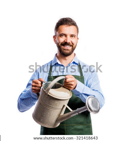 Young handsome gardener in green apron. Studio shot on white background - stock photo
