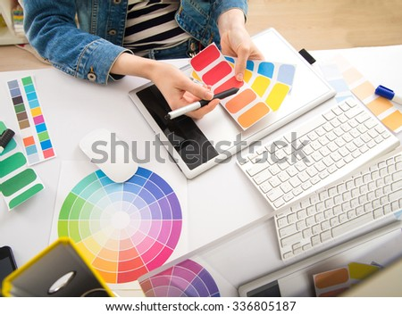 Young Handsome Graphic designer using graphics tablet to do his work at desk - stock photo
