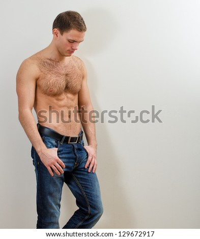 Young handsome guy in jeans with bare torso against the wall - stock photo