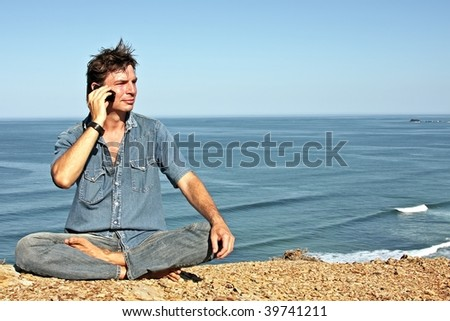 Young handsome guy making a phonecall on the rocks at the ocean - stock photo
