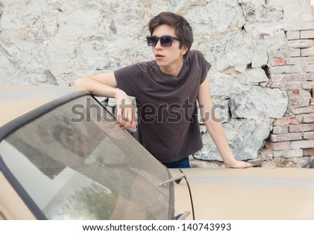 young handsome guy next to an old broken CAR - stock photo