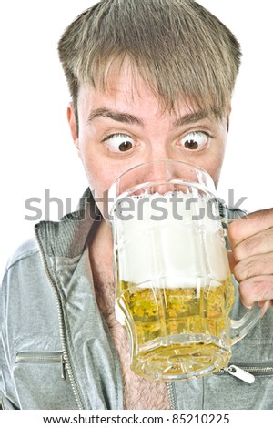 young handsome guy standing and drinking beer from a large mug, isolated over white - stock photo