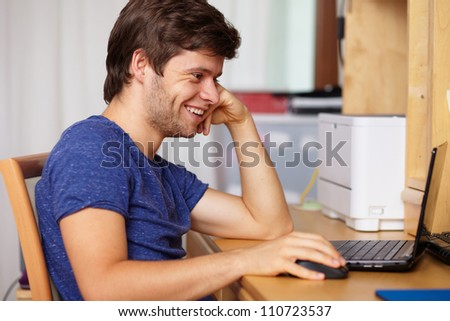 Young handsome guy with laptop next to table in room, background - stock photo