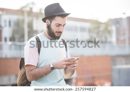 young handsome hipster gay modern man using smartphone in town - stock photo