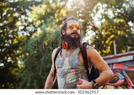 Young handsome hipster man relaxed at sunny day on the park, after football training, wearing stylish shirt and sunglasses, listening music,and enjoy his holiday.Reflecting Sunglasses - stock photo
