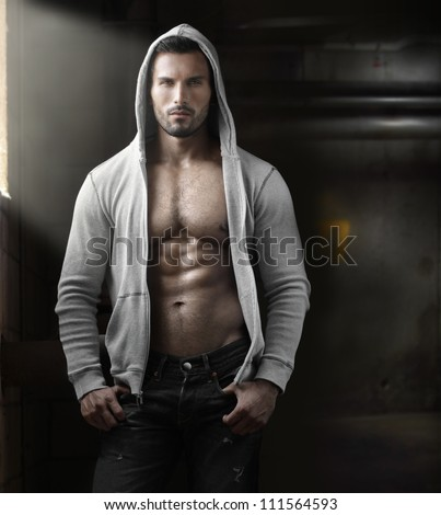 Young handsome macho man with open jacket revealing muscular chest and abs in industrial garage with window light - stock photo