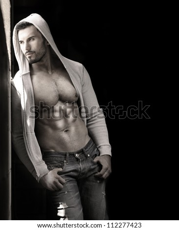 Young handsome macho man with open jacket revealing muscular chest and abs with copy space - stock photo