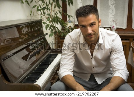 Young handsome male artist smiling while sitting next to his wooden classical upright piano, indoor portrait - stock photo