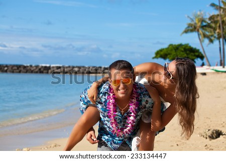 Young handsome male carrying female piggyback style on the Hawaiian beach. Playful love. Feeling young and free - stock photo