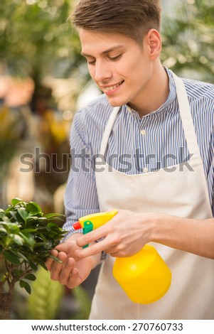 Young handsome male florist spraying flower in shop. - stock photo