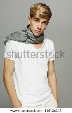 Young handsome male in shorts and scarf over the posing with hands in pockets - stock photo