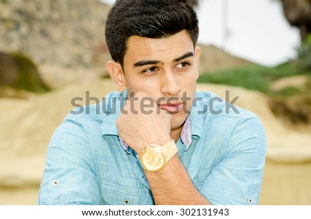 Young handsome male with dark hair and dark eyes, thinking  - stock photo