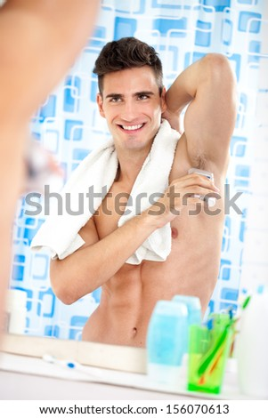 young handsome man applying roll-on antiperspirant on armpit - stock photo