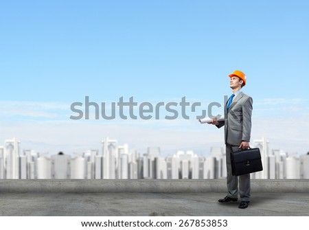 Young handsome man architect in hardhat with project in hand - stock photo