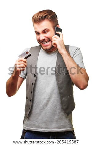 Young handsome man arguing by phone holding banking card in his hand. Isolated on white background. - stock photo