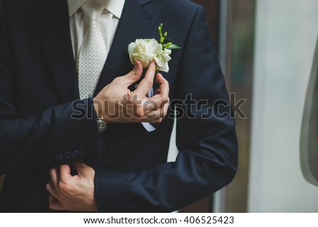 young handsome man being beautiful bride dressed in wedding day standing next to the window and adjusts Boutonnière Carmen in her black jacket - stock photo