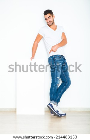 Young handsome man casual dressed smiling and showing a blank panel on white background - stock photo